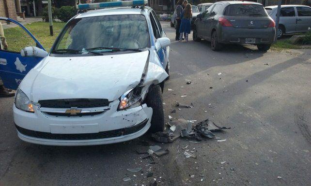 El patrullero quedó dañado en su parte delantera. Al fondo se ve el auto de la funcionaria municipal.