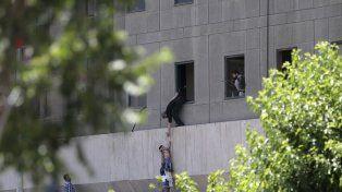 Un niño es rescatado por un civil y un guardia en el parlamento iraquí.