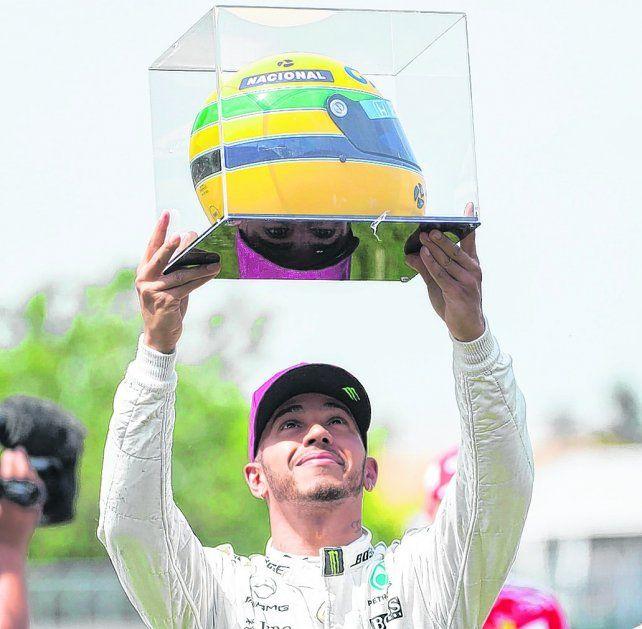 Bien en alto. Hamilton muestra orgulloso el casco que le hizo llegar la familia del brasileño