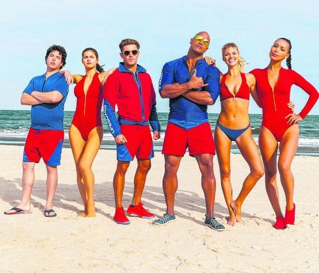 A pleno sol. Zac Efron y Dwayne Johnson (en el centro) acompañados por las chicas de la nueva generación.