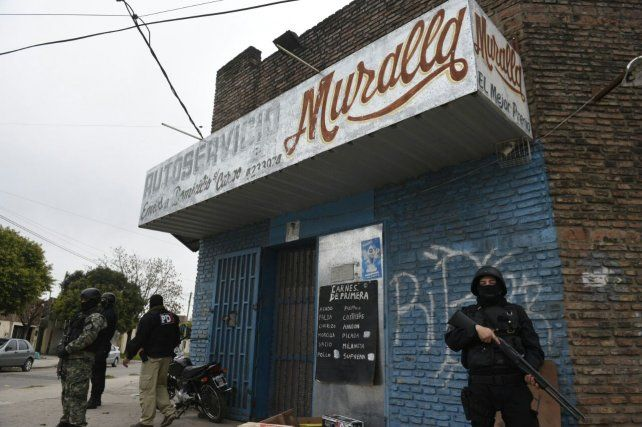 Efectivos policiales custodian uno de los locales allanados esta mañana.