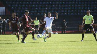 Nacho busca el balón ante un defensor. Scocco fue decisivo en el gol de Fértoli.