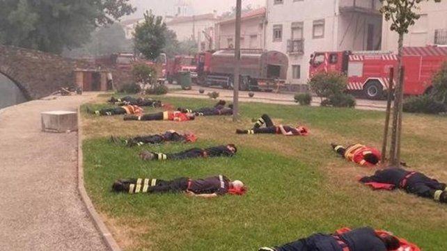 Un instante de descanso. Los bomberos descansan mientras reabastecen con agua los camiones.