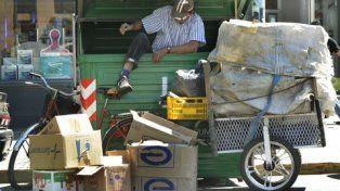 desde adentro. Un recolector busca en el interior de un contenedor de basura objetos para reciclar y comercializar en el mercado informal.