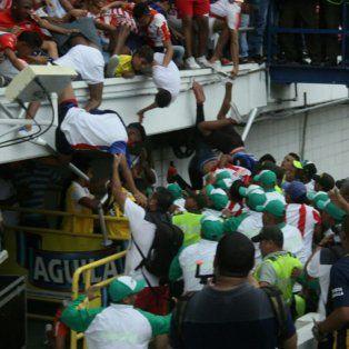 El momento en que los hinchas se caen desde la tribuna y quedan heridos.