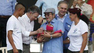 Reconciliación. Santos sonríe a un bebé sostenido por el líder de las Farc