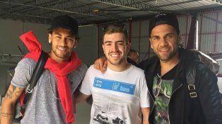 La llegada. Neymar y Dani Alves junto a un fanático que les pidió una foto en el aeropuerto.