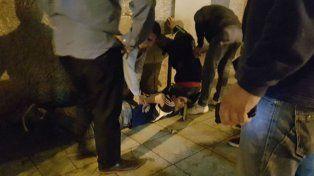 El ladrón yace en el suelo detenido por personas que se encontraban en el lugar.