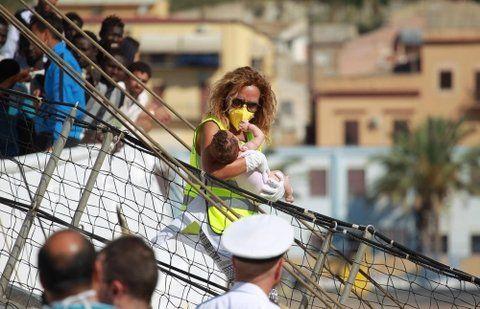 no me llames extranjero. Una inmigrante proveniente de España baja con su bebé en un puerto en Sicilia.