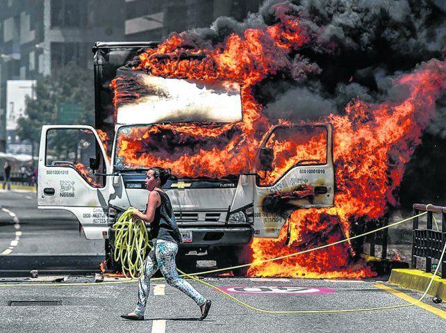 Tensión social. Un vehículo arde en Caracas durante el bloqueo de rutas convocado por la oposición.