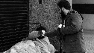Voluntarios de Rosario Solidaria reparten el desayuno a quienes padecen el frío.
