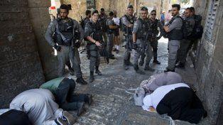 Protestas. Israelíes vigilan a palestinos que rezan en la Puerta de los Leones, en la ciudad vieja de Jerusalén