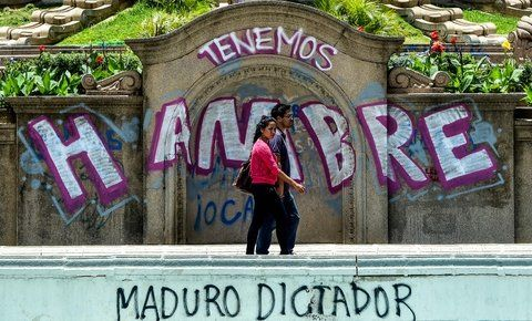 Conflictividad. Una pareja de venezolanos cruza frente a un mural que denuncia la crítica situación.