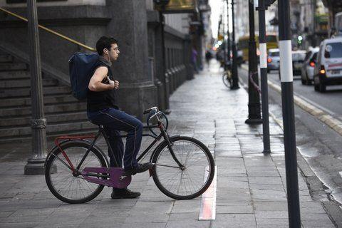 cumplidor. Un muchacho aguarda paciente destrás de la tira de Led que se instaló en el piso en la intersección de Corrientes y Córdoba. Sólo la minoría respeta este semáforo.