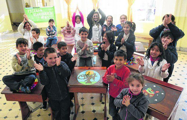 Chicos de la Escuela Echeverría junto a los pupitres que pintaron para obsequiar en la fiesta del centenario.