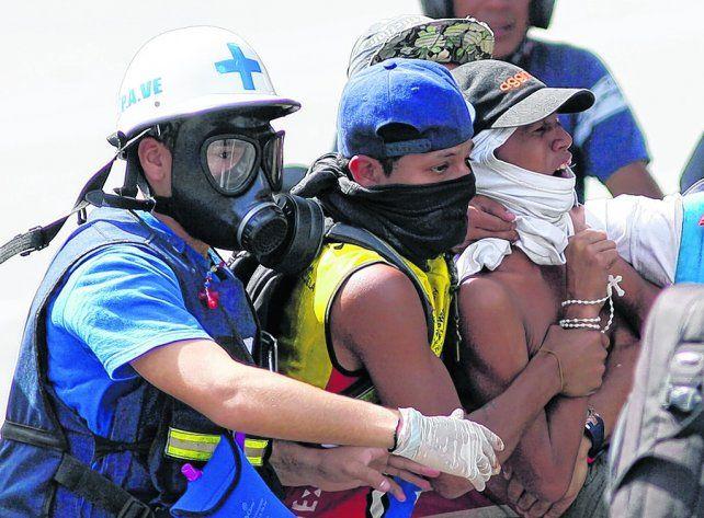 Tensión. Dos jóvenes venezolanos son evacuados tras resultar herido uno de ellos durante una manifestación.