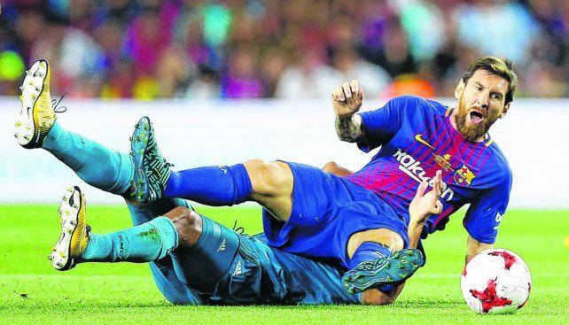 Por el piso. Lionel Messi cae derribado por un defensor merengue. Ayer el rosarino intentó por todos los medios guiar a Barcelona pero no alcanzó.