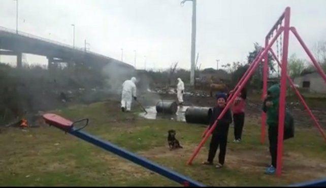 Imagen de celular. Operarios vestidos de blanco volcaron y quemaron los tachos a metros de los niños.