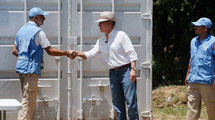 Bien hecho. Santos (der.) estrecha la mano al jefe de misión de la ONU frente al último contenedor de armas.