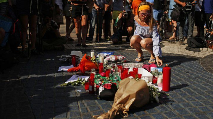 Una mujer deja una ofrenda floral en frente a la Catedral de la Sagrada Familia.