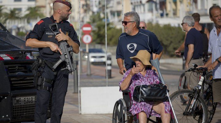 Un hombre empuja a una mujer en silla de ruedas y recibe información de un policía en Cambrils