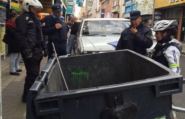 Pleno centro de la ciudad de Córdoba. Policías examinan el contenedor donde apareció la criatura.