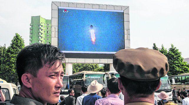 ¿Preludio de ataque? Norcoreanos observan en una pantalla gigante el ensayo misilístico que sobrevoló Japón.