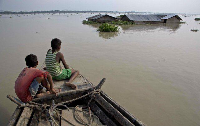 En bote. Niños navegan por la ciudad de Morigaon