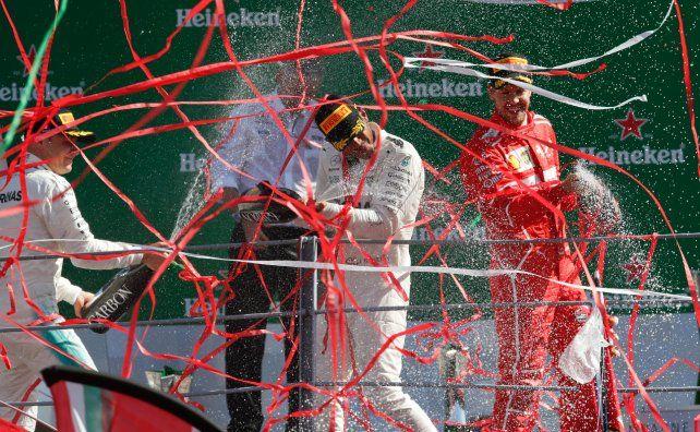 Serpentinas y champán. Hamilton festeja en el podio con Valtteri Bottas y Sebastian Vettel.