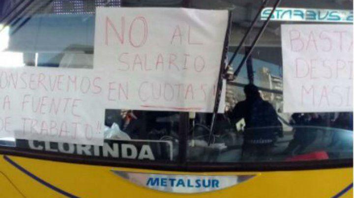 Los trabajadores pegaron pancartas en el parabrisas de los micros para exhibir sus reclamos.