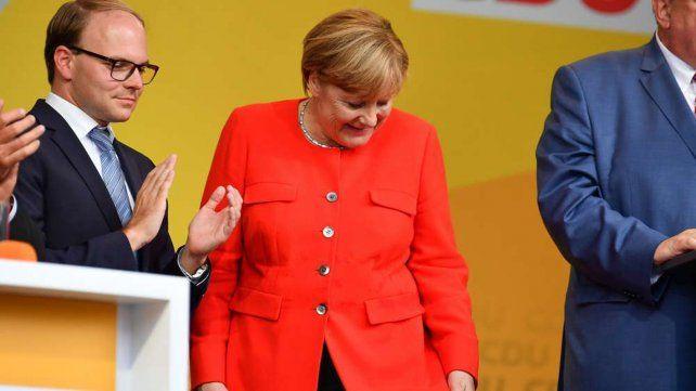 La canciller alemana se cerciora si alguno de los tomates dio en el objetivo.