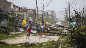 Peligro. Una mamá y su pequeño caminan cerca de líneas eléctricas derribadas por el huracán en la localidad de Caibarien.