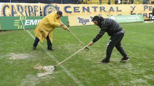 De la línea para afuera. Los trabajadores quitan el agua a contrarreloj a minutos del inicio del juego.