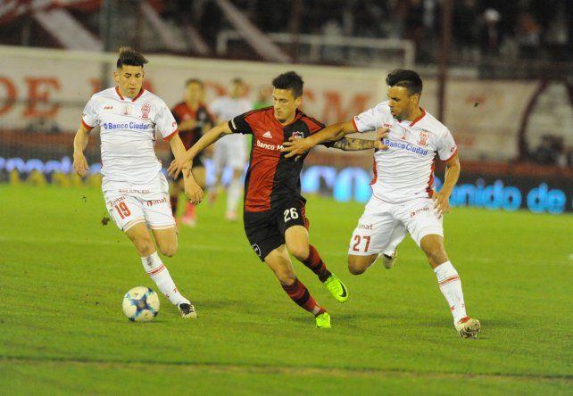 Héctor Fértoli intenta escapar ante la marca de Calello y Villalba.