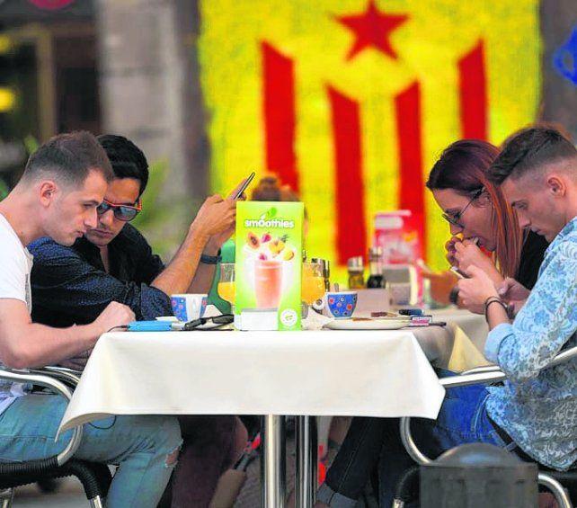División. Turistas sentados frente a una estelada en Barcelona