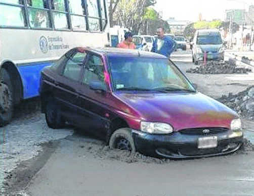 Un Ford Escort quedó hundido de trompa en el cemento.
