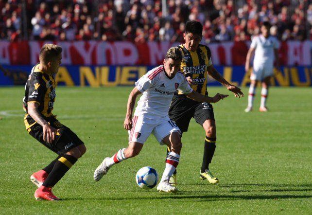 Joaquín Torres maniobra ante la marca de dos futbolistas de Olimpo.