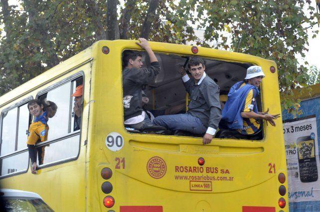 Hinchas viajan hacia la cancha a bordo de un ómnibus al que le sacaron la luneta trasera. Muchas veces también se suben al techo.