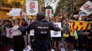 Tensión. Un agente de la Guardia Civil intenta detener el avance de manifestantes que protestaban frente a una de las sedes de gobierno requisadas.