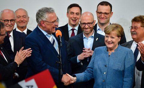 felices. Merkel y su aliado bávaro de la CSU se felicitan mutuamente anoche en Berlín.