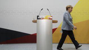 serenidad. Merkel se retira luego de dar su conferencia de prensa. Atrás la frase El Centro