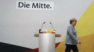 Merkel se retira luego de dar su conferencia de prensa. Atrás la frase El Centro