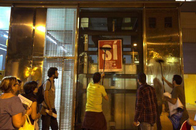 Decididos. Jóvenes catalanes pegan afiches a favor del voto por el sí.