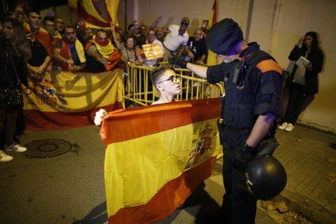 Por la unión. Un policía catalán pide a una joven que retroceda.
