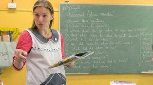 teacher. Una profesora al frente de una clase. El sistema educativo presenta fallas y carencias en cuanto a metas y evaluaciones.