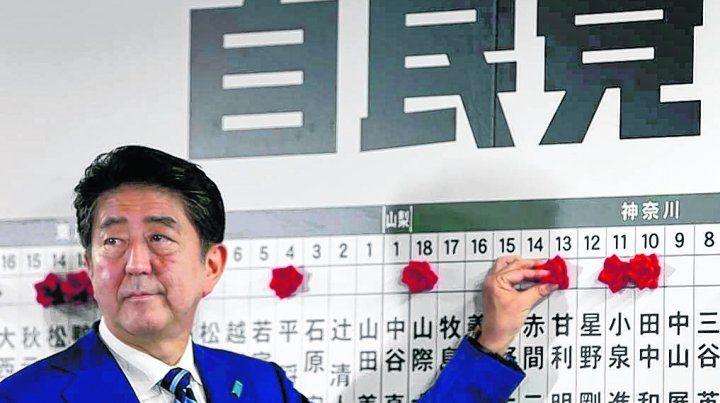 triunfante. El premier liberal conservador japonés ante el tablero que marca los resultados por distrito.