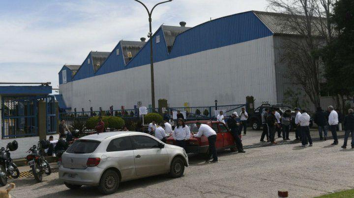 Los empleados de Unilever se mantienen en el portón de acceso a la planta.