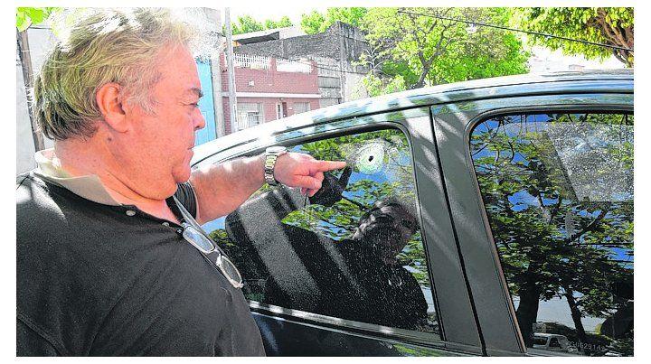 impacto. Un vecino muestra el orificio que dejó un balazo en su auto.