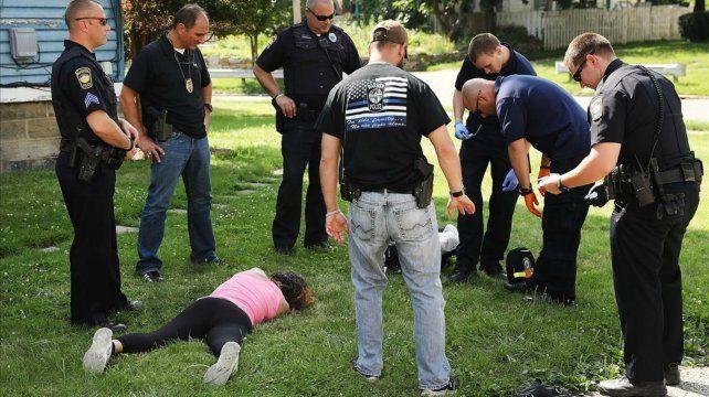 inconsciente. Trabajadores sanitarios y policías atienden a una mujer víctima de una sobredosis de heroína