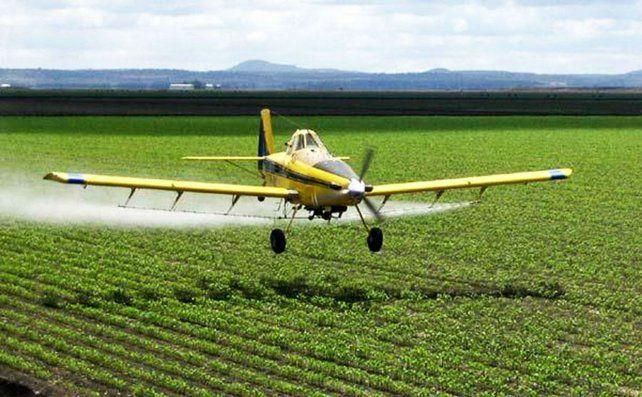 Pesticidas. Un avión fumiga un campo sembrado